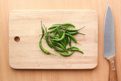 Green chilli peppers on wooden chopping board Royalty Free Stock Image