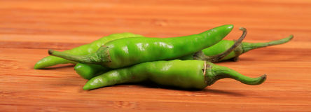Green chillies. Lying over wooden surface Royalty Free Stock Images