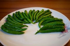 Green chillies arranged in beautiful pattern on a plate royalty free stock photos