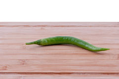 Green chillieson chopping board. Green chillies on aged chopping boarrd on white background. horizontal Royalty Free Stock Photos