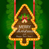 Green Christmas background with golden bells. Abstract green background with fir tree branches, snowflakes, retro lights on wooden banner in the form of Stock Photo