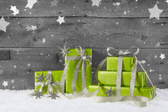 Green christmas background on grey wooden background with snow. stock photo