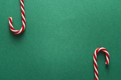 Green Christmas background with red candy canes. Copy space. Chr Stock Image