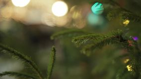 Green Christmas Ball. Close up shot of green christmas ball hanging on a fir tree branch against background with colorful bokeh lights stock video footage