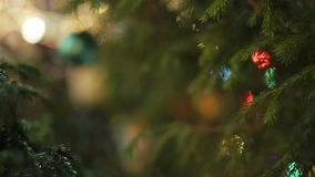 Green Christmas Ball. Close up shot of green christmas ball hanging on a fir tree branch against background with colorful bokeh lights stock video