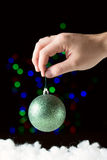 Green christmas ball in the hand  on the black background. With colorful bokeh Royalty Free Stock Images