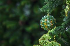 Green christmas ball hanging on a Christmas tree, modern ball decorated with crystals royalty free stock image