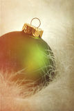 Green Christmas Ball On Soft Feathers Stock Photos