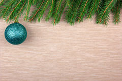 Green Christmas ball on a  textile background with snow fir tree. Top view, space for your text. Christmas background with snow fir tree Royalty Free Stock Image