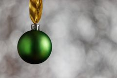 Green Christmas ball on a white bokeh background similar to snowflakes. There is space for copy space next to the Christmas ball.  royalty free stock images