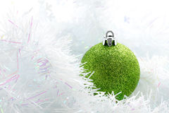 Green christmas ball on white brunch background. Single green christmas ball on white brunch background in a soft atmosphere Royalty Free Stock Images