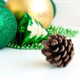 Green Christmas balls and fir-cone. Stock Photos