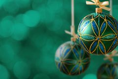 Green christmas balls hanging on abstract background. Copy space Stock Images