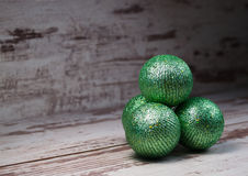 Green christmas balls in a stack over wooden background Royalty Free Stock Photo