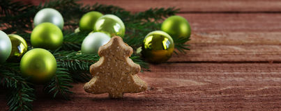 Green christmas baubles  in fir branches and a small Christmas t. Ree made of gingerbread on a rustic wooden table, banner or website header with copy space Stock Photo