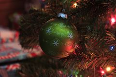 Green Christmas Bulb closeup on a Christmas Tree. A Green Christmas Bulb shot closeup on a Christmas Tree with lights, thats bright and colorful Royalty Free Stock Photos