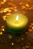 Green Christmas candle burning with glowing light. Surrounded by small golden decorative star shapes, high-angle close-up royalty free stock image
