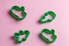 Green christmas cookie cutters on the pink table. stock photo