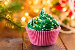 Green christmas cupcake with bokeh on background royalty free stock images