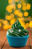 Green christmas cupcake with bokeh on background royalty free stock photography