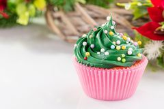 Green christmas cupcake with colorful sprinkles in pink cup stock photo