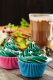 Green christmas cupcake with festive decorations and glass of co royalty free stock images