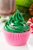 Green christmas cupcake with star sprinkles in pink cup. On white background with festive decorations and glass of coffee Stock Images