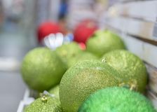 Green Christmas decorations in box. Colorful baubles in the white box.  stock image