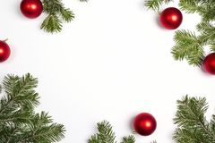 Green Christmas fir tree branches with red balls and copy space. Christmas green framework isolated on white background. Top view, flat lay Stock Images