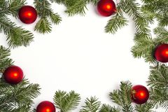 Green Christmas fir tree branches with red balls and copy space. Christmas green framework isolated on white background Royalty Free Stock Photo