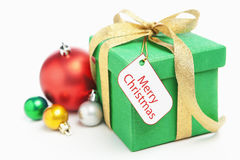 Green Christmas gift with ornament and tag. Isolated over white royalty free stock images