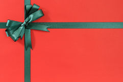Green Christmas gift ribbon bow on plain red background paper, copy space Royalty Free Stock Photography