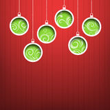 Green Christmas hanging balls on red background Stock Images