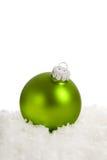 Green Christmas ornament on snow Stock Image