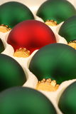 Green Christmas Ornaments with One Red. A close-up of a package of Green Christmas Tree Ornaments with an individual Red one Stock Photos