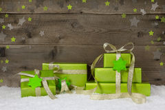Green christmas presents with snow on wooden background. Stock Photography