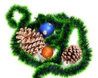 Green Christmas tinsel, Christmas-tree balls and big pine cones Royalty Free Stock Image