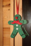 Green Christmas toy man. In a wooden house Stock Photos