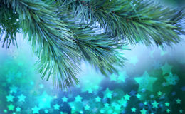 Green Christmas Tree Background. A Christmas tree branch with glowing stars and snowflakes in the background Royalty Free Stock Images