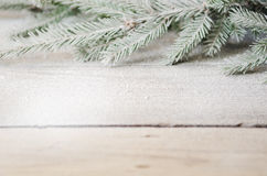 Green Christmas tree branch with snow on a wooden Royalty Free Stock Photos