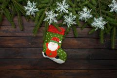 Green Christmas tree branches on a dark wooden background. New Year background with sock and white snowflakes. Top view Stock Photos