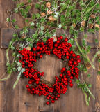 Green christmas tree branches and wreath from red berries Royalty Free Stock Photo
