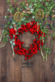 Green christmas tree branches and wreath from red berries Stock Photos
