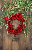 Green christmas tree branches and wreath from red berries Royalty Free Stock Images