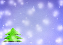 Green Christmas tree cut from plush material on the surface of blue paper and falling snow Stock Images