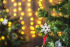 Green Christmas tree decorated with Christmas toys and a garland with yellow lights. Stock Photos