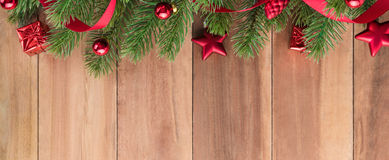 Green Christmas tree leaves with shiny red ornaments on wood bacground Royalty Free Stock Photo