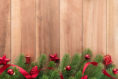 Green Christmas tree leaves with shiny red ornaments on wood background Stock Image