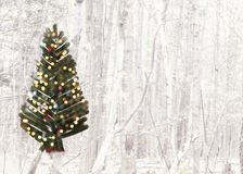 Christmas card with tree brushed onto a background of forest landscape. Green Christmas tree with lights brushed onto a white festive forest scene Royalty Free Stock Photos
