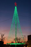Green christmas tree made out of LEDs in front of a sky colored. A modern christmas tree with a red star on a Spanish Christmas market. Sun has just set in the stock photography